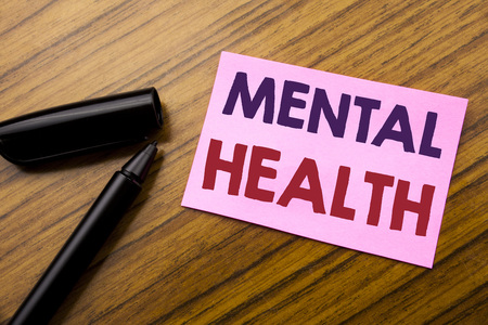 Word, writing Mental Health. Business concept for Anxiety Illness Disorder Written on sticky note red paper, wooden background pen. Note stick on the desk.