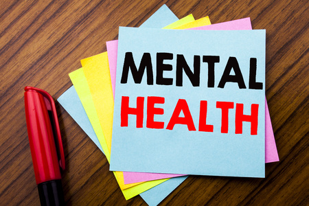 Handwriting Announcement text Mental Health.  Concept for Anxiety Illness Disorder Written on sticky stick note with wooden background with space office view with pencil marker