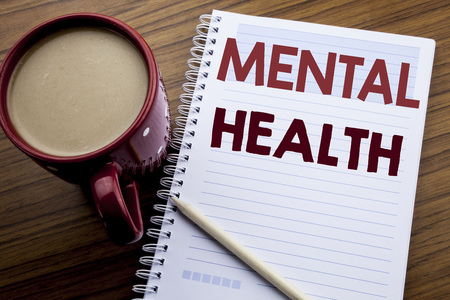 Hand writing text caption inspiration showing Mental Health. Business concept for Anxiety Illness Disorder written on note paper notepad on the wooden background with coffee and pen. 写真素材