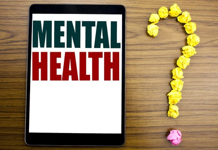 Word, writing Mental Health. Business concept for Anxiety Illness Disorder Written on tablet, background with question mark on the end.