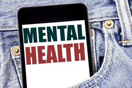 Hand writing text caption inspiration showing Mental Health. Business concept for Anxiety Illness Disorder written on smartphone in jeans pants. Blue background.