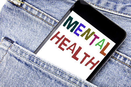 Handwriting Announcement text showing Mental Health. Business concept for Anxiety Illness Disorder Written phone mobile phone, cellphone placed in man front jeans pocket. 写真素材