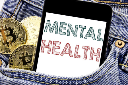 Hand writing text caption inspiration showing Mental Health. Business concept for Anxiety Illness Disorder Written phone mobile phone, cellphone placed in man front jeans pocket.