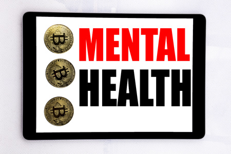 Writing text showing Mental Health. Business concept for Anxiety Illness Disorder written on tablet screen on white background with cryptocurrency bitcoin next to it.