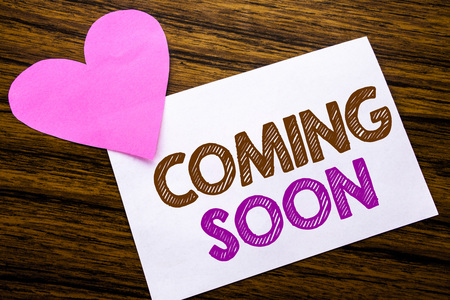 Conceptual hand writing text showing Coming Soon. Concept for Message Future written on sticky note paper, wooden background. With pink heart meaning love adoration.