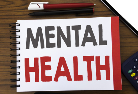Handwritten text showing Mental Health. Business concept writing for Anxiety Illness Disorder Written on notepad paper, wooden background in office view with pencil marker calculator