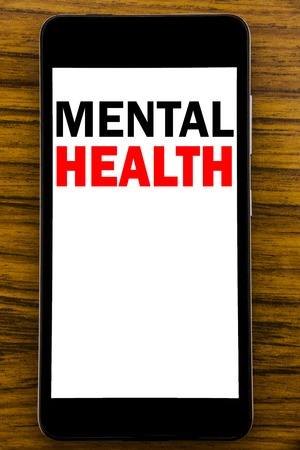 Handwriting Announcement text showing Mental Health. Business concept for Anxiety Illness Disorder Written on mobile cellphone with wooden background with space on the table