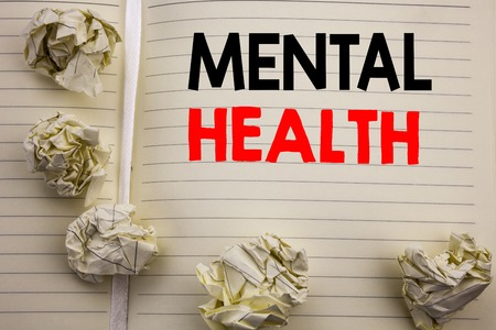 Handwritten text showing Mental Health. Business concept writing for Anxiety Illness Disorder Written on notepad paper, white background with space and office view.
