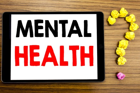 Writing text showing Mental Health. Business concept for Anxiety Illness Disorder written on tablet computer on wooden background with question mark made of folded paper.