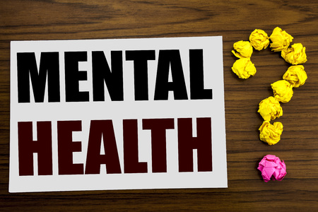 Hand writing text caption inspiration showing Mental Health. Business concept for Anxiety Illness Disorder written on white paper on the wooden background with question mark on the end.