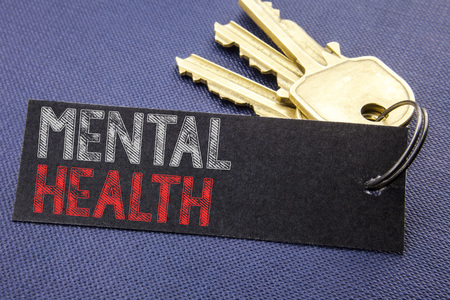 Handwritten text showing Mental Health. Business concept writing for Anxiety Illness Disorder Written on note paper attached to key, black background with space close up