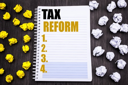 Conceptual hand writing text caption showing Tax Reform. Business concept for Government Change in Taxes Written notepad note notebook book wooden background with sticky folded yellow and white