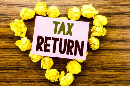 Word, writing Tax Return. Business concept for Taxation Refund written on sticky note paper on wooden background. Stock Photo