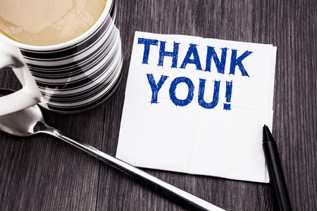 Handwritten text showing Thank You. Business concept for Thanks Message written on tissue paper handkerchief on the wooden wood background. With marker and coffee. Office top view. 写真素材 - 96166324