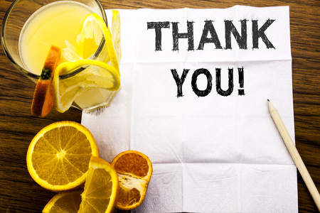 Conceptual text caption showing Thank You. Concept for Thanks Message written on tissue paper on wooden background with pen healthy juice and orange fruit in the restaurant