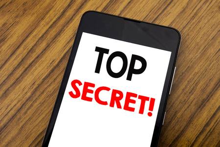 Word, writing handwriting Top Secret. Business concept for Military Top Secret Written on mobile phone, wooden background with copy space. Stock Photo