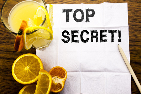 Conceptual text caption showing Top Secret. Concept for Military Top Secret written on tissue paper on wooden background with pen healthy juice and orange fruit in the restaurant Stock Photo