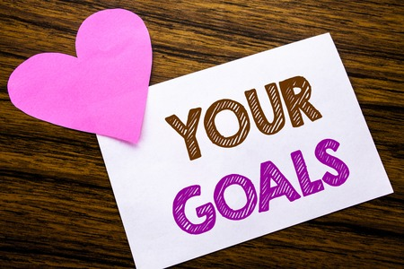 Conceptual hand writing text showing Your Golas. Concept for Goal Achievement written on sticky note paper, wooden background. With pink heart meaning love adoration. Stock Photo