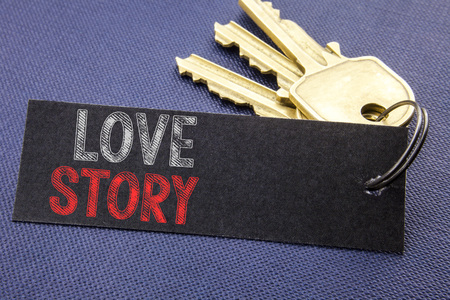 Handwritten text showing Love Story. Business concept writing for Loving Someone Heart  Written on note paper attached to key, black background with space close up Stock Photo