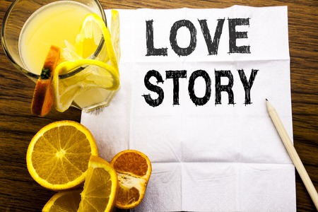 Conceptual text caption showing Love Story. Concept for Loving Someone Heart  written on tissue paper on wooden background with pen healthy juice and orange fruit in the restaurant