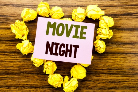 Word, writing Movie Night. Business concept for Wathing Movies  written on sticky note paper on wooden background.