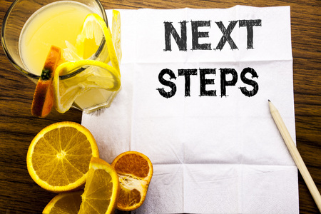 Conceptual text caption showing Next Steps. Concept for Future Golas and Target written on tissue paper on wooden background with pen healthy juice and orange fruit in the restaurant