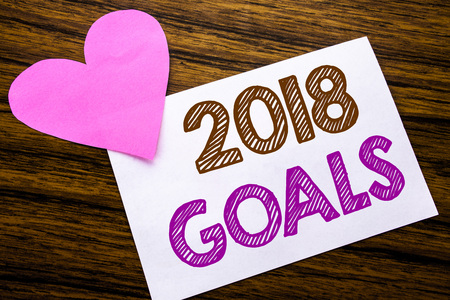 Conceptual hand writing text showing 2018 Goals. Concept for New Yer resolutions written on sticky note paper, wooden background. With pink heart meaning love adoration. Stock Photo