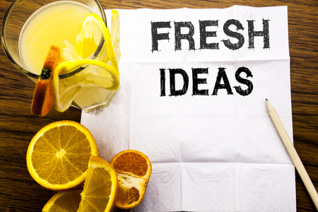 Conceptual text caption showing Fresh Ideas. Concept for Thinking Inspiration Inspire Creativity written on tissue paper on wooden background with pen healthy juice and orange fruit in the restaurant