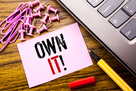 Handwritten text showing Own It Exclamation. Business concept for Ownership Control written on pink sticky note paper on wooden background next to keyboard. With red pen.