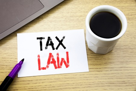 Tax Law. Business concept for Taxation Taxes Rule written on notebook book on wooden background in the Office with laptop coffee