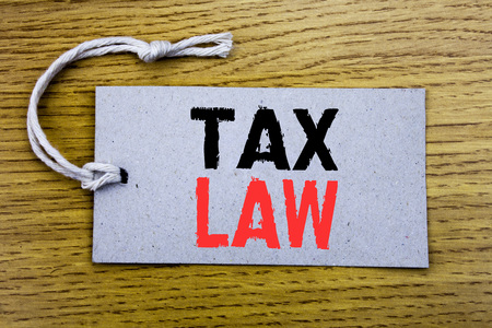 Conceptual hand writing text caption showing Tax Law. Business concept for Taxation Taxes Rule written on price tag paper with copy space on wooden vintage background