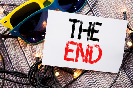 Writing text showing The End. Business concept for End Finish Close written on old wood wooden background with sunglasses
