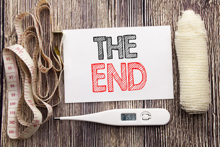 Handwritten text showing The End. Business fitness health concept writing for End Finish Close written on wood wooden background with bandage and thermometer