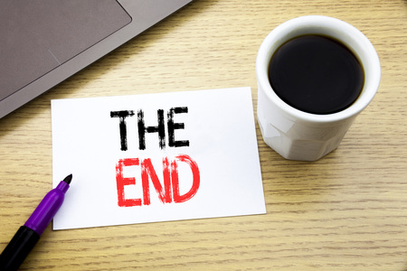 Handwriting Announcement text showing The End. Business concept for End Finish Close written on notebook book on wooden background in the Office with laptop coffee