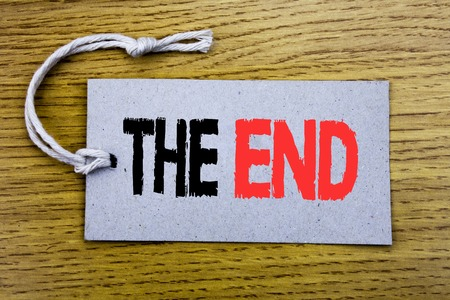 Conceptual hand writing text caption showing The End. Business concept for End Finish Close written on price tag paper with copy space on wooden vintage background