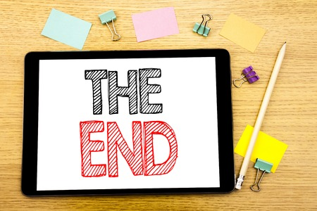 Writing text showing The End. Business concept for End Finish Close Written on tablet, wooden background with sticky note and pen