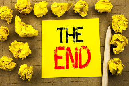 The End. Business concept for End Finish Close written on sticky note paper on vintage background. Folded yellow papers on the background
