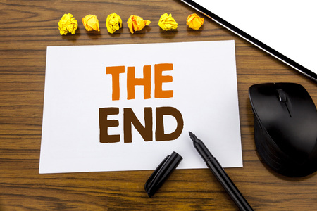 Conceptual hand writing text showing The End. Business concept for End Finish Close written on sticky note paper on wooden background with marker mouse and tablet office view.