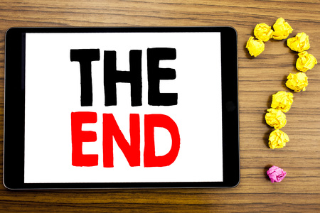 Writing text showing The End. Business concept for End Finish Close written on tablet computer on wooden background with question mark made of folded paper.