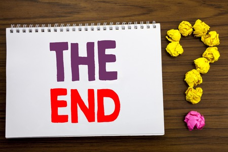 Conceptual hand writing caption inspiration showing The End. Business concept for End Finish Close written on notepad paper on the wooden background with question mark.