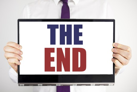 Word, writing The End. Business concept for End Finish Close Written on tablet laptop holding by man blurred background. Businessman fingers keeping the computer.
