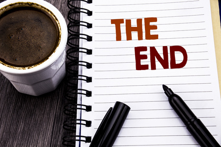 Writing text showing The End. Business concept for End Finish Close written on notebook book note paper on wooden wood background. With coffee and black marker.