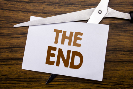 Hand writing text caption inspiration showing The End. Business concept for End Finish Close Written on note, wooden with colourful scissors meaning destroy stop of something.