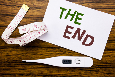 Conceptual hand writing text caption showing The End. Business concept for End Finish Close written on sticky note paper wood background. Meter and thermometer for fitness subject. Banco de Imagens