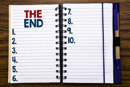 Writing text showing The End. Business concept for End Finish Close Written on notebook paper, wooden background with pen and marker. Banco de Imagens