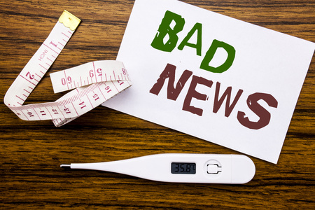 Conceptual hand writing text caption showing Bad News. Business concept for Failure Media Newspaper written on sticky note paper wood background. Meter and thermometer for fitness subject.