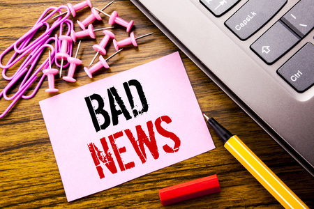 Handwritten text showing Bad News. Business concept for Failure Media Newspaper written on pink sticky note paper on wooden background next to keyboard. With red pen.