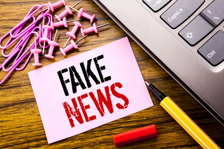 Handwritten text showing Fake News. Business concept for Hoax Journalism written on pink sticky note paper on wooden background next to keyboard. With red pen. Stock Photo