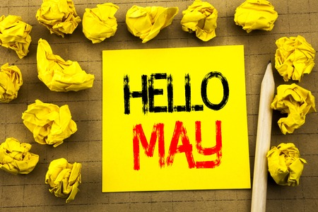 Hello May Month. Business concept for Coming Spring Month written on sticky note paper on vintage background. Folded yellow papers on the background