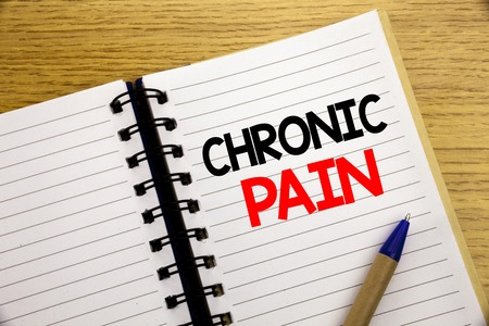 Word, writing Chronic Pain. Business concept for Feeling Bad ill Care written on notepad with space on old wood wooden background with pen marker